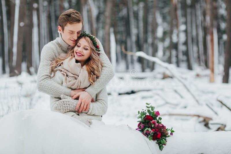 Bruden och brudgummen kramar i vinterskognärbilden Vinterbröllopceremoni royaltyfri fotografi