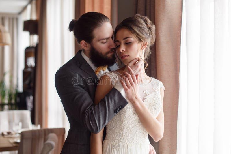 Bruden och brudgummen kramar sig på fönstret Brudgummen slår bruden i framsidan Storen specificerar royaltyfria bilder