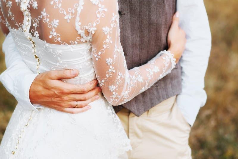 Bruden och brudgummen kramar sig täta händer upp royaltyfri bild