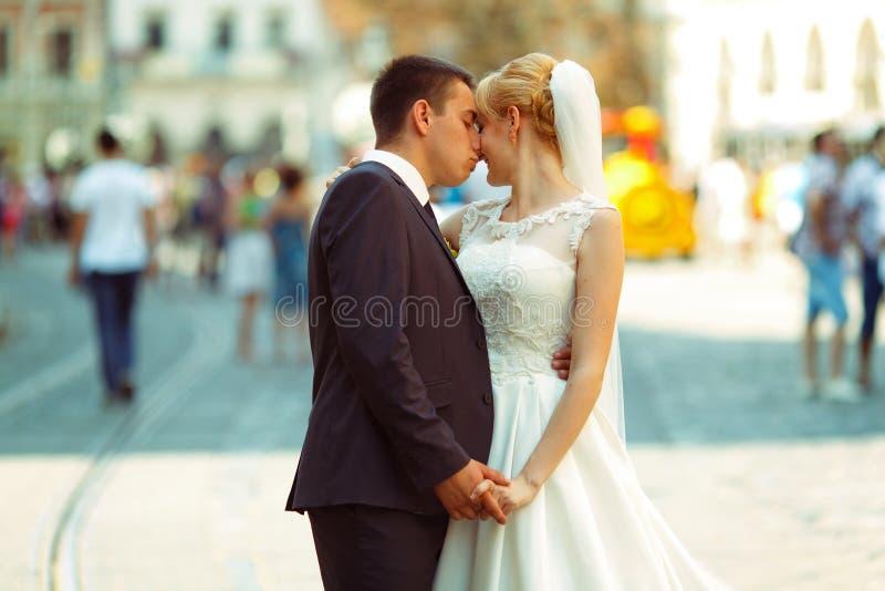Bruden och brudgummen kysser att rymma deras händer som står tillsammans på th royaltyfri foto