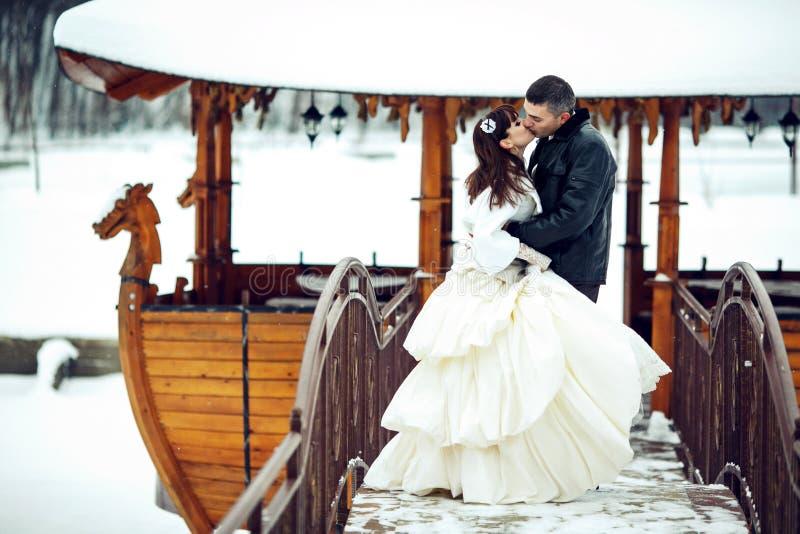 Bruden och brudgummen kysser framtill av ett träfartyg som täckas med royaltyfria bilder