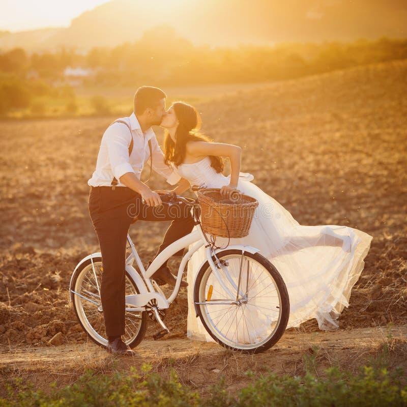 Bruden och brudgummen med ett vitt bröllop cyklar fotografering för bildbyråer