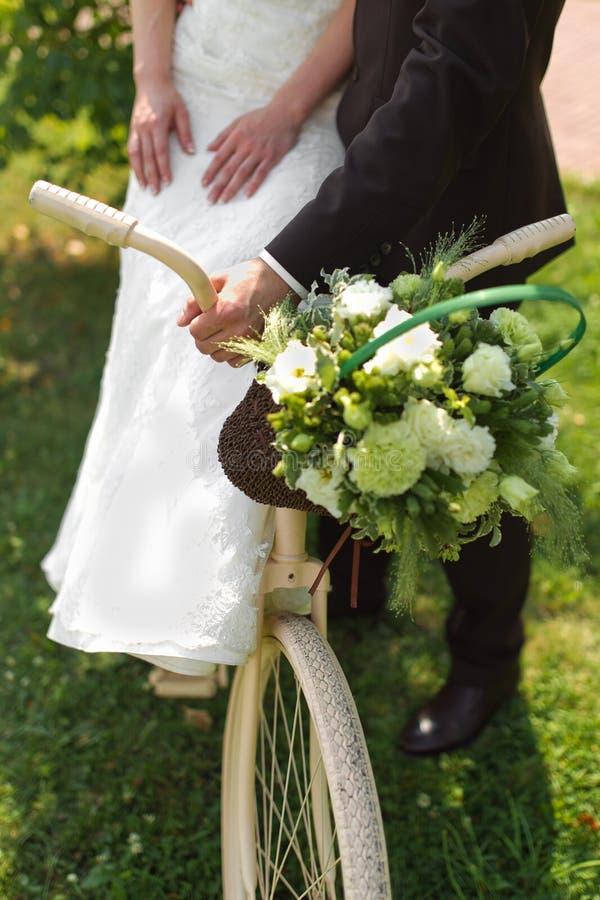 Bruden och brudgummen med ett vitt bröllop cyklar royaltyfri bild