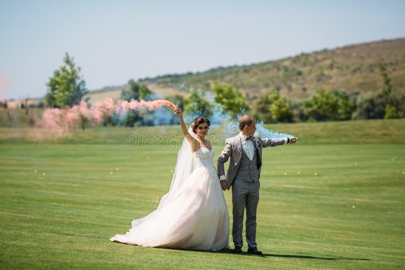 Bruden och brudgummen med rök bombarderar på ett fält med grönt gräs Nygifta personer som utomhus går på bröllopdagen flicka in arkivbilder
