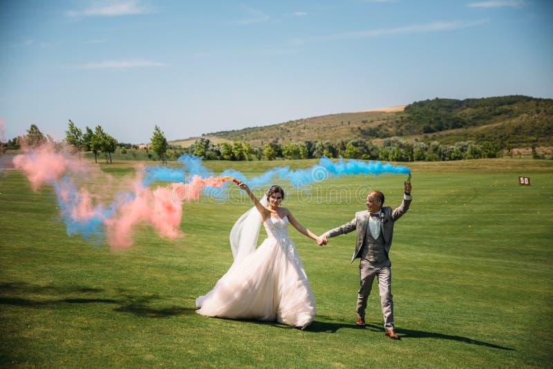 Bruden och brudgummen med rök bombarderar på ett fält med grönt gräs Nygifta personer som utomhus går på bröllopdagen flicka in arkivfoton