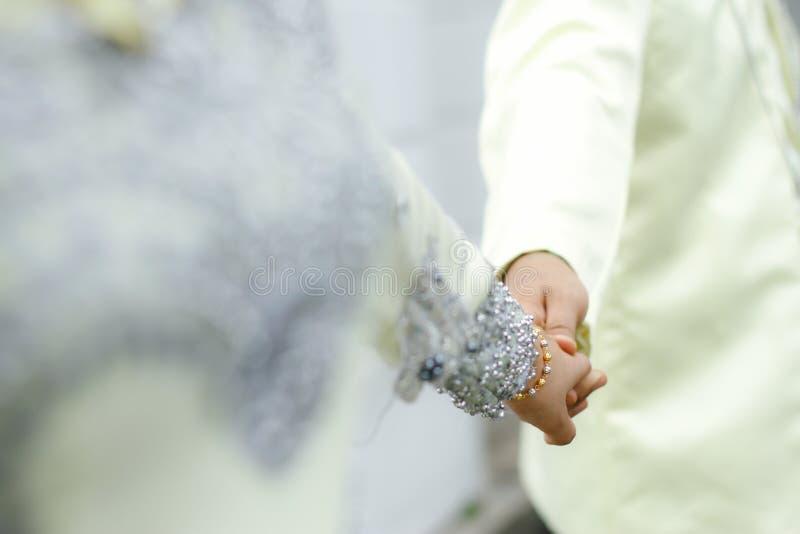Bruden och brudgummen, når de har gifta sig hållen, räcker tillsammans royaltyfria foton