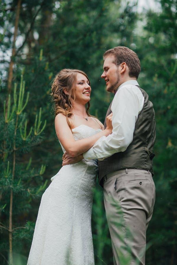 Bruden och brudgummen omfamnar mot bakgrundsskogen royaltyfria bilder