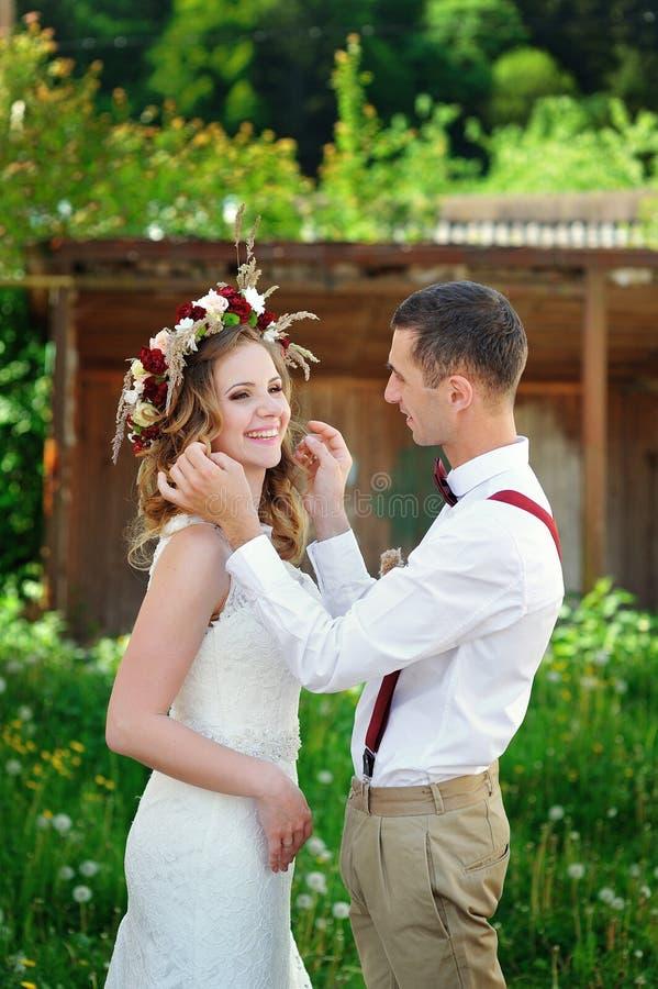 Bruden och brudgummen på bröllopdagen som utomhus går på våren, parkerar arkivbild
