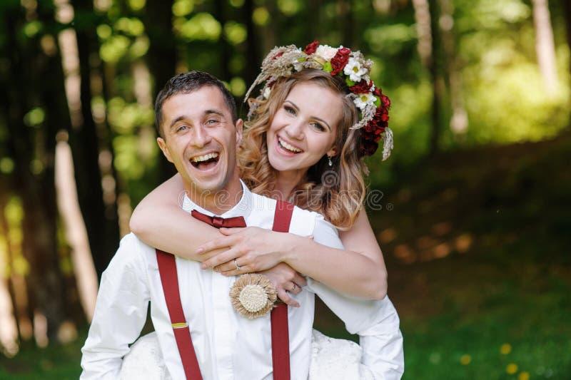 Bruden och brudgummen på bröllopdagen som utomhus går på våren, parkerar arkivfoto