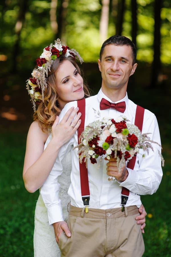 Bruden och brudgummen på bröllopdagen som utomhus går på våren, parkerar royaltyfri foto