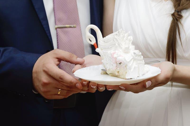 Bruden och brudgummen rymmer ett stycke av bröllopstårtan, närbild arkivfoto