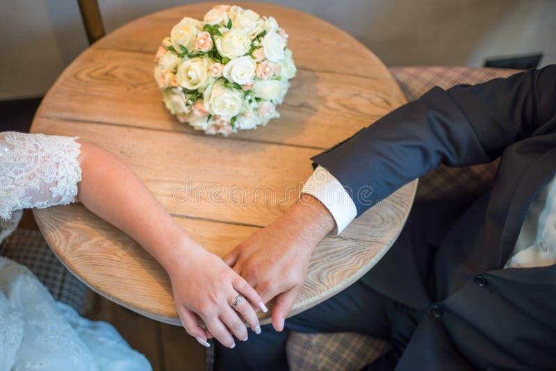 Bruden och brudgummen rymmer varje - annan räcker sittande tabell Nära bröllopbukett royaltyfri bild