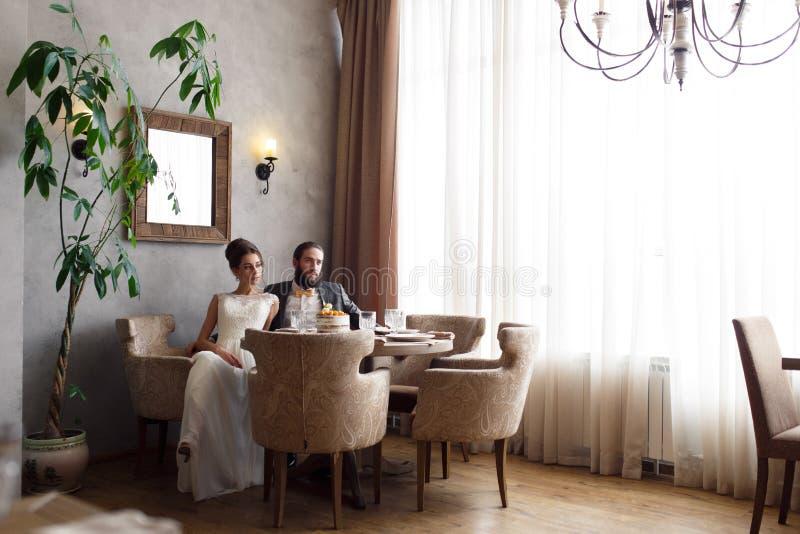 Bruden och brudgummen sitter i fåtöljer på tabellen i en härlig ljus korridor royaltyfria foton