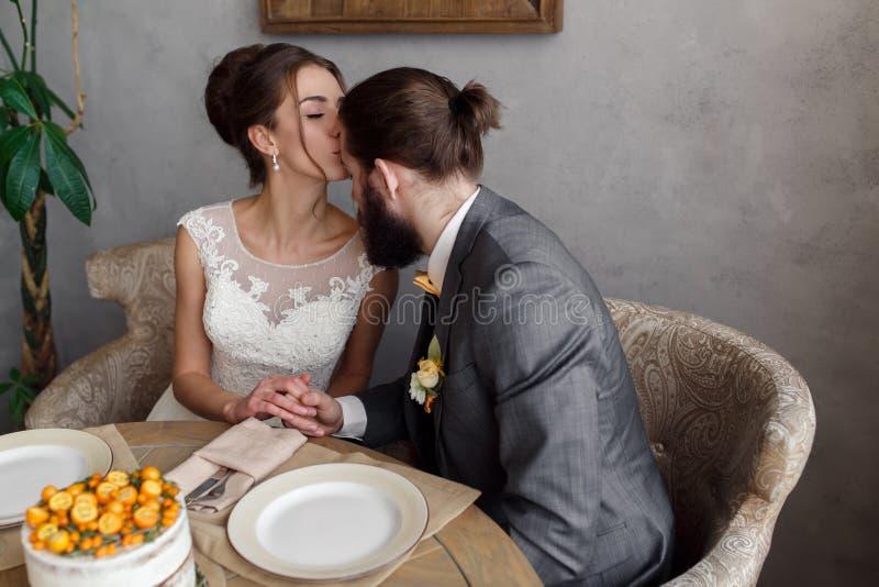 Bruden och brudgummen sitter på tabellen på tabellen Bruden kysser brudgummen på pannan royaltyfri foto