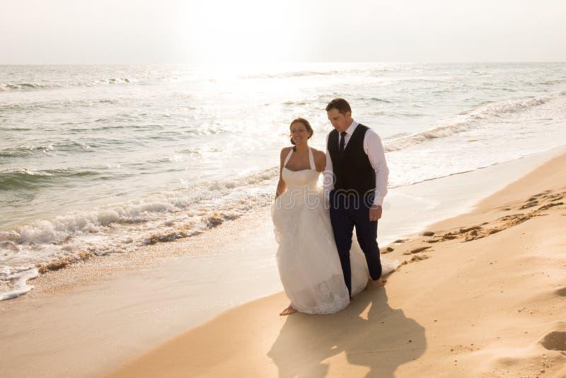 Bruden och brudgummen som går på solnedgången på en härlig tropisk strandromantiker, att gifta sig arkivbilder