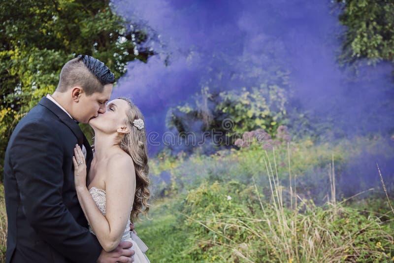 Bruden och brudgummen som kysser i skog med lilor, röker arkivfoton