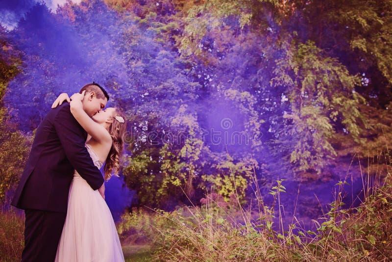 Bruden och brudgummen som kysser i skog med lilor, röker arkivfoto
