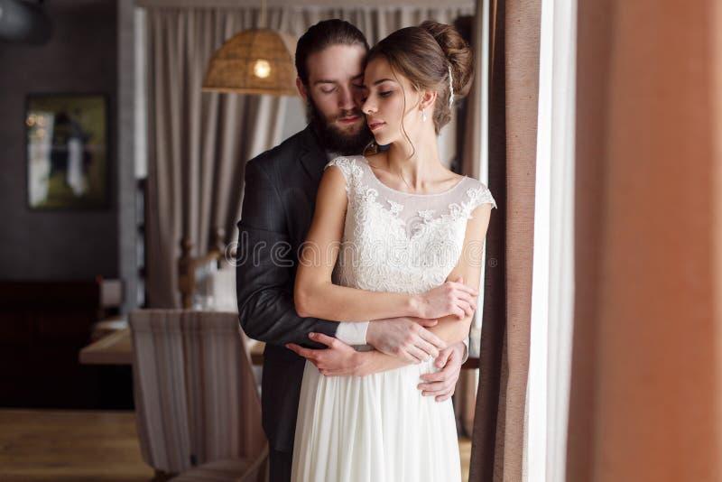 Bruden och brudgummen står i ett rum vid fönstret Brudgummen kramar bruden från baksidan fotografering för bildbyråer