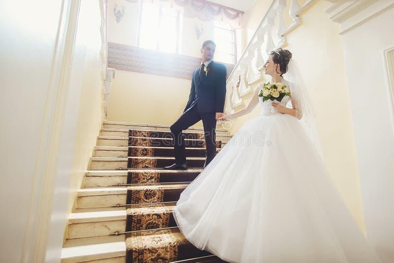 Bruden och brudgummen står på trappuppgång, rymmer händer och ser de royaltyfri fotografi