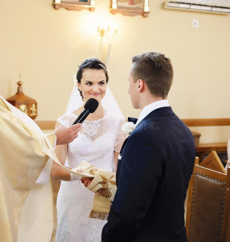 Bruden och brudgummen under bröllopceremonin i kyrkan royaltyfri bild