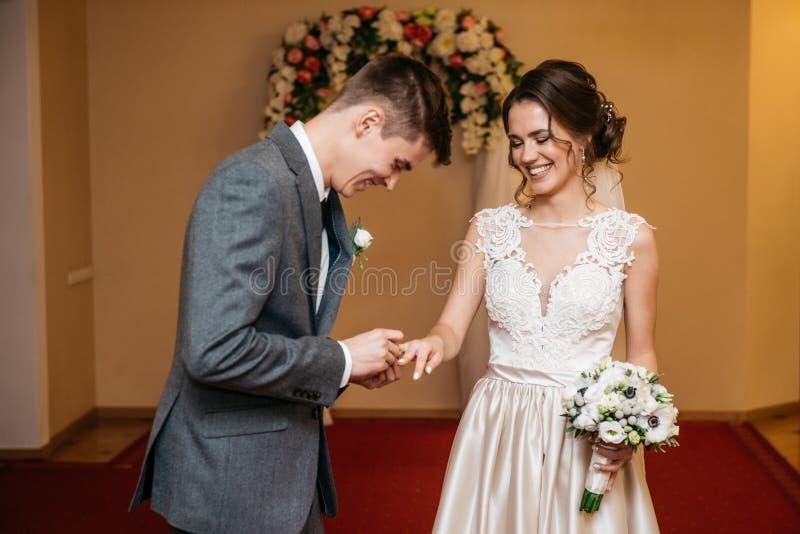 Bruden och brudgummen utbyter vigselringar i registreringskontoret royaltyfria foton