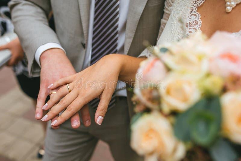 Bruden och brudgummen visar deras händer med guld- cirklar nära bröllopbuketten royaltyfria foton