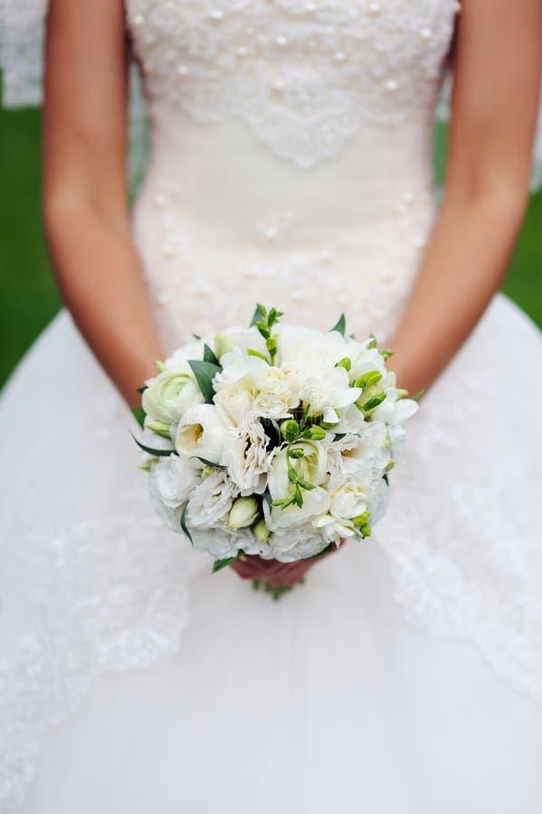 Bruden räcker den hållande buketten fotografering för bildbyråer