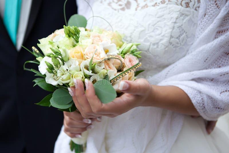 Bruden rymmer en bröllopbukett arkivbild