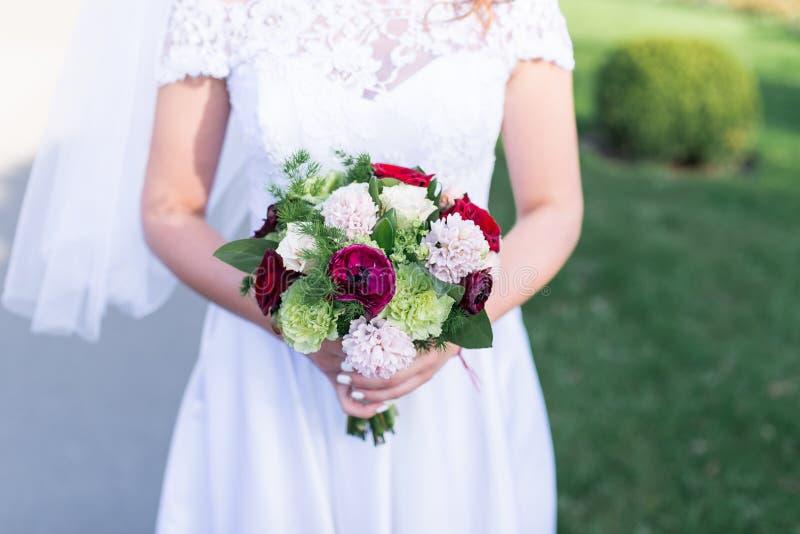 Bruden rymmer en bröllopbukett med vit, rosa färger, röda blommor och grönska royaltyfri bild