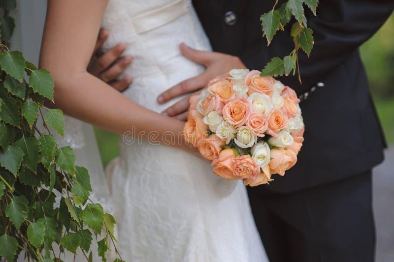 Bruden rymmer en bröllopbukett och ett exponeringsglas av champagne royaltyfri foto