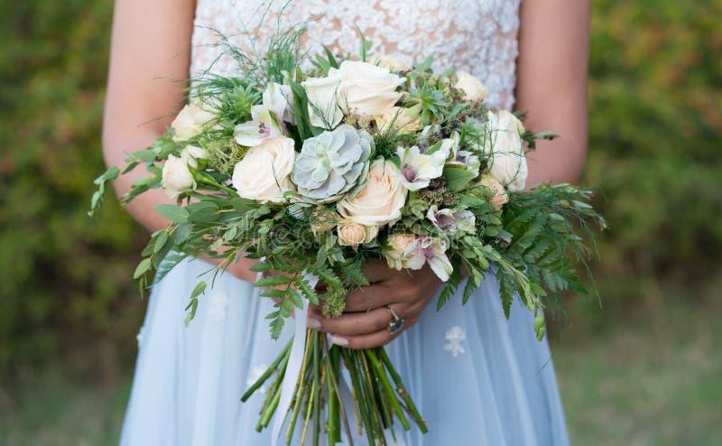 Bruden rymmer en lantlig gifta sig bukett med suckulentblommor och grönska arkivfoton