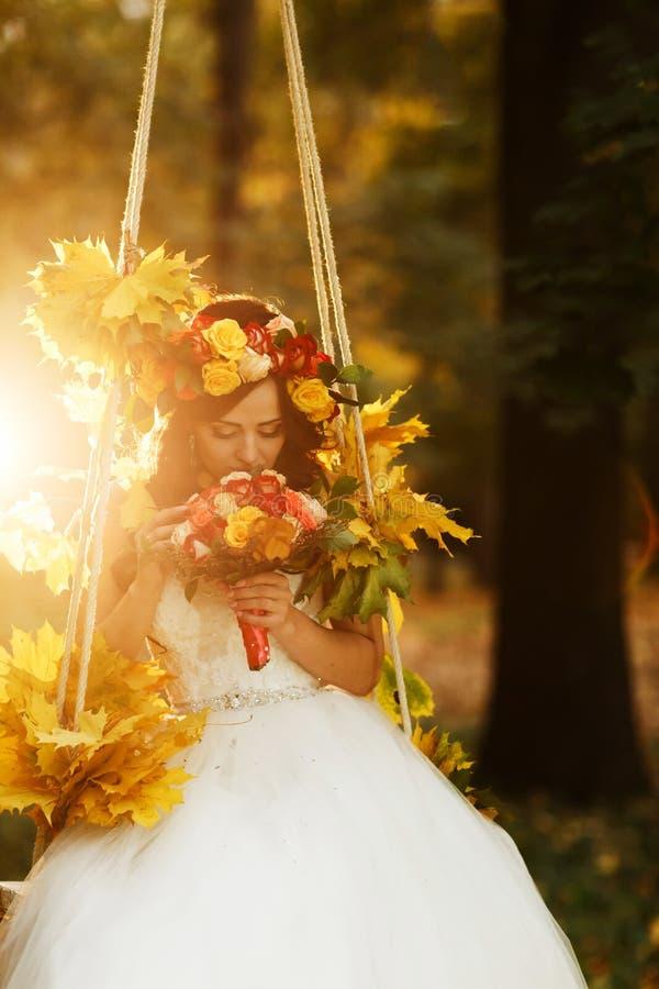 Bruden rymmer en röd bröllopbouqet i henne armar som sitter på swinen royaltyfria bilder