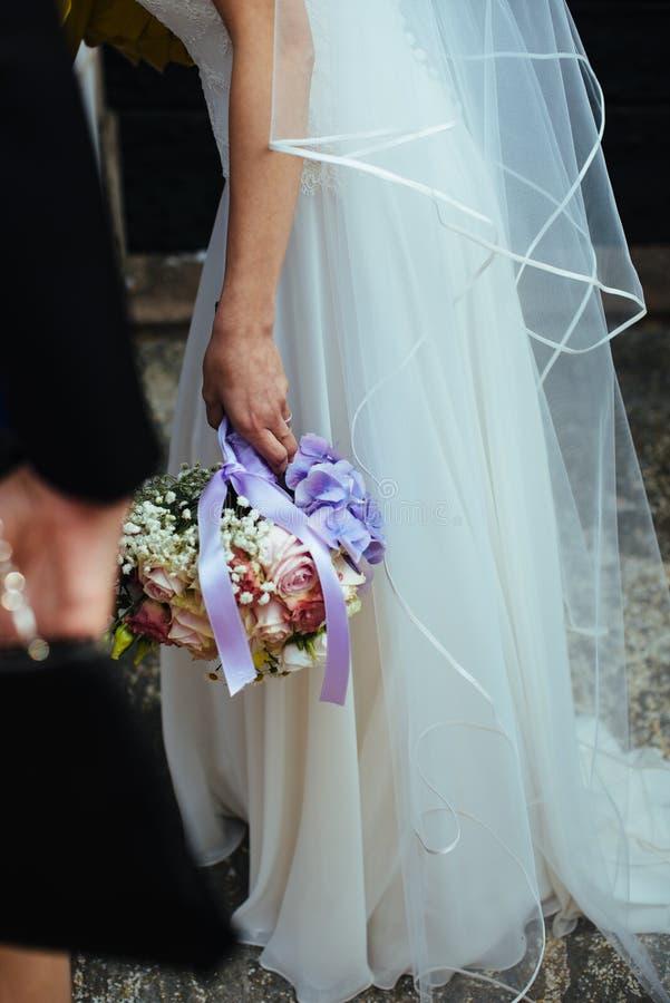 bruden rymmer hennes bukett av blommor med murgrönarostusenskönor och hy royaltyfria bilder