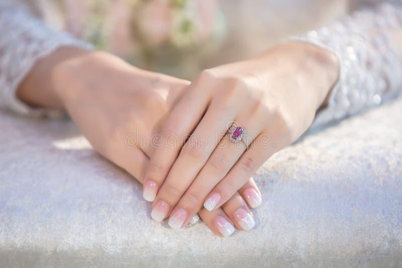 Bruden rymmer hennes hand på en vit härlig brud- klänning och visar arkivbilder