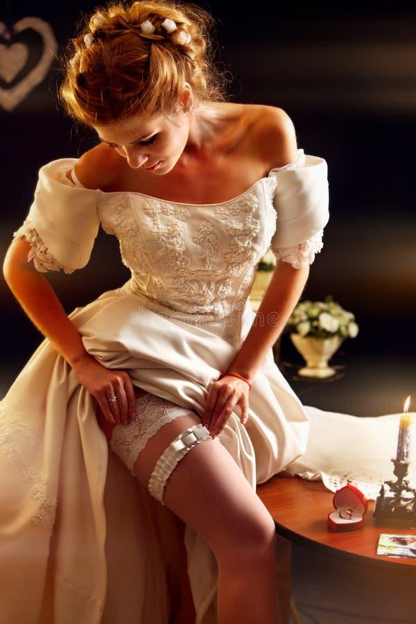 Bruden sätter den brud- strumpebandet för bröllopceremoni royaltyfri bild