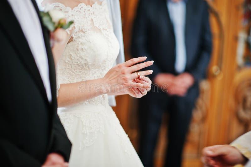 Bruden sätter vigselringen på handen på kyrka arkivbilder