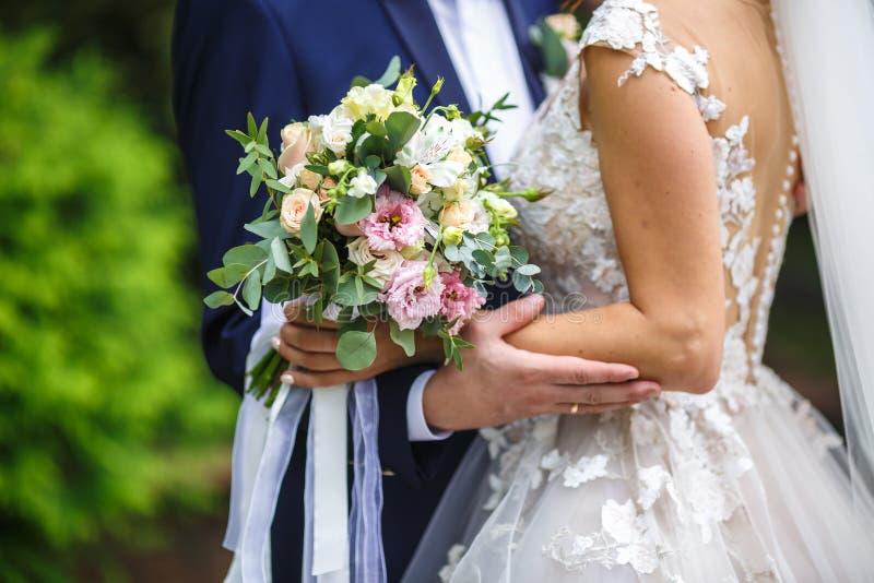 Bruden satte hennes händer på skuldrorna av brudgummen brud med en bukett av kramar för rosa och vita rosor och att kyssa brudgum royaltyfria foton