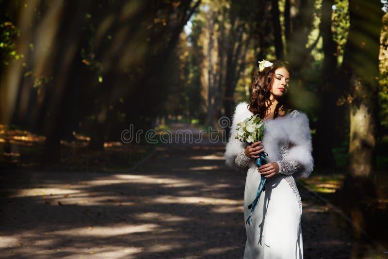 Bruden ser det sinnliga innehavet en liljabukett royaltyfria bilder