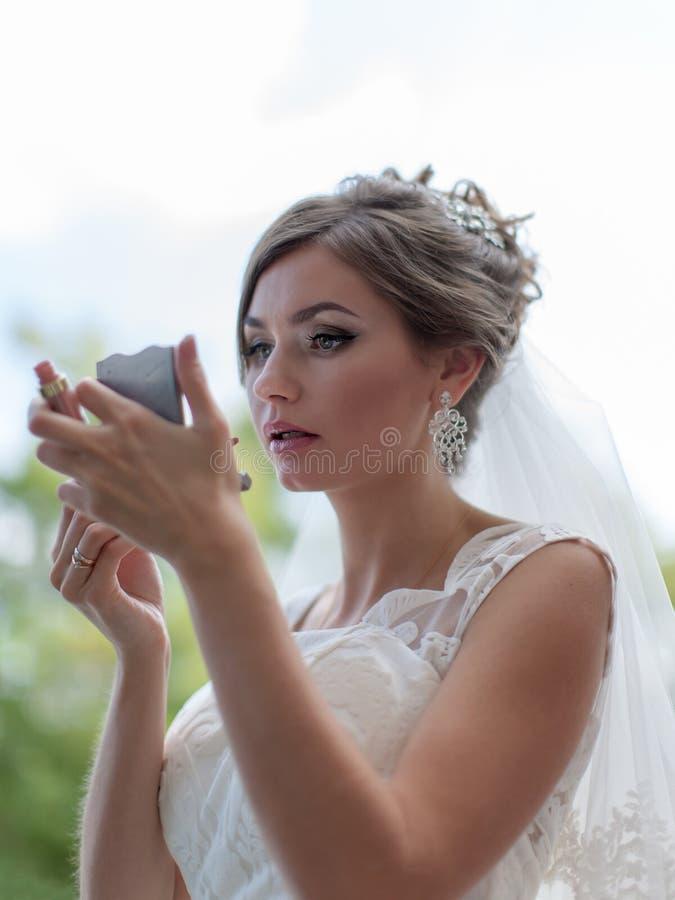 Bruden ser i spegel och korrigerar makeup fotografering för bildbyråer