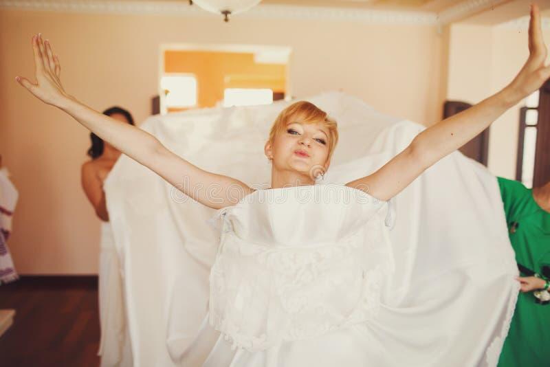 Bruden ser roligt sätta på en bröllopsklänning arkivbild