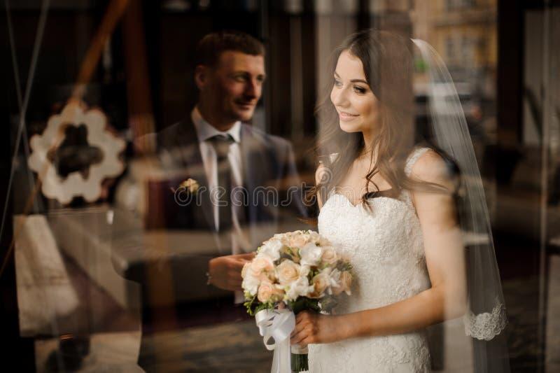 Bruden ser ut fönstret på reflexionen av brudgummen royaltyfria bilder