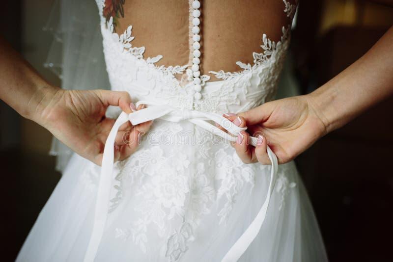 Bruden själv binder en pilbågebröllopsklänning royaltyfri foto