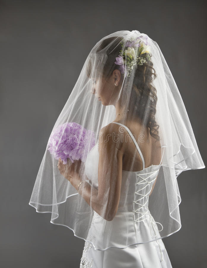 Bruden skyler ståenden som gifta sig brud- hårstil, blommabuketten royaltyfri fotografi