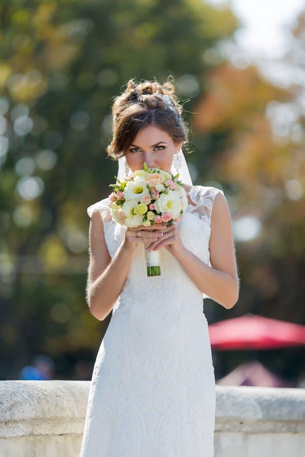 Bruden sniffar brud- liten bukett på öppen luft royaltyfria foton