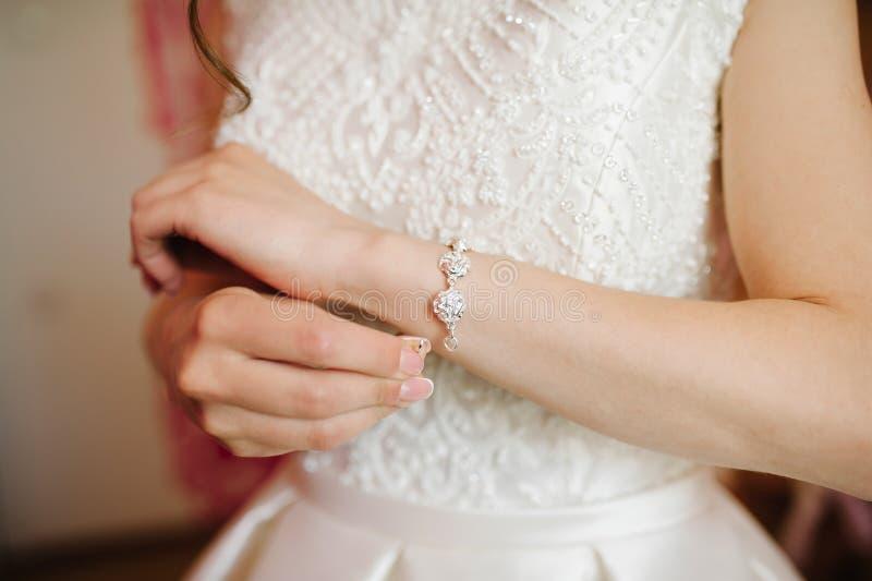 Bruden som får armbandet, klädde på hennes bröllopdag fotografering för bildbyråer