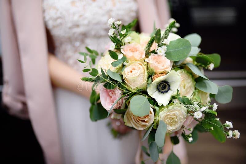Bruden som rymmer stilfullt bröllop, blommar buketten arkivbild