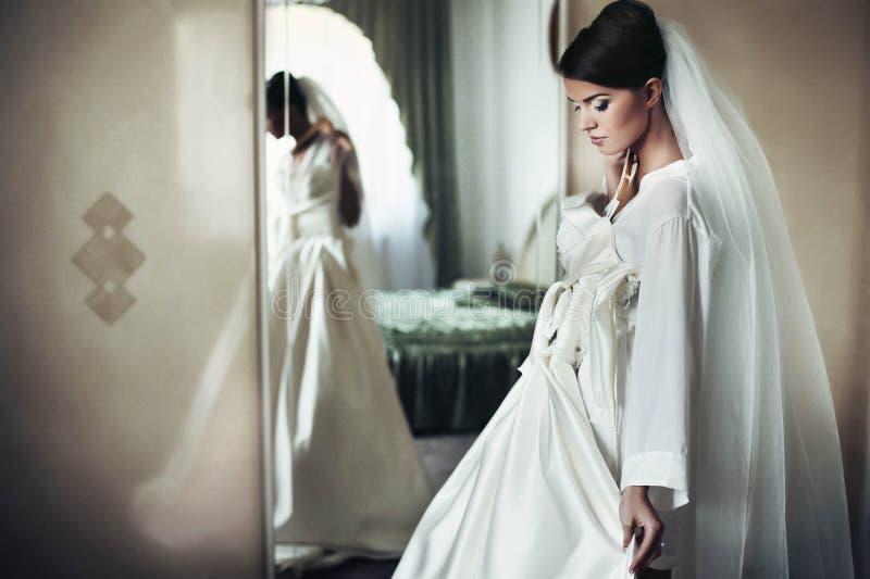 Bruden tar bort bröllopsklänningen royaltyfri foto