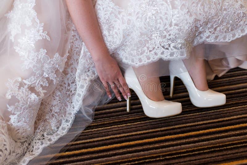 Bruden trycker på hennes vita bröllopskor bröllop för tappning för klädpardag lyckligt arkivfoto