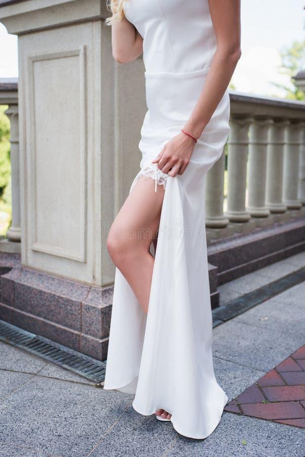 Bruden visar henne att garvade det slanka benet med strumpebandet arkivfoton