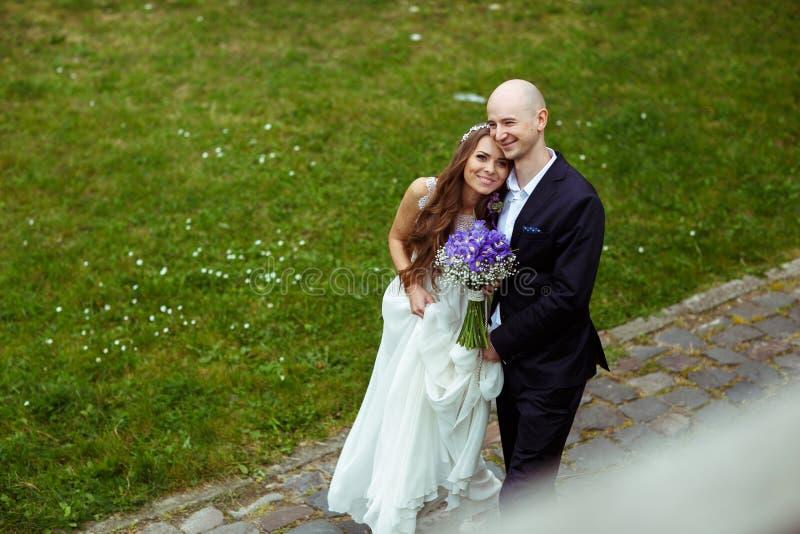 Brudens framsida skiner, medan gromm kramar hennes anseende på banan in royaltyfria bilder